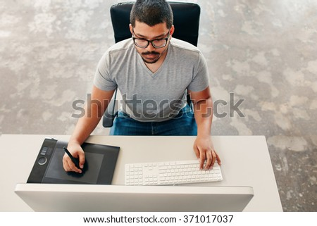 High angle image of young man using a stylus and tablet while working on his computer. Graphic designer working at his desk. - stock photo