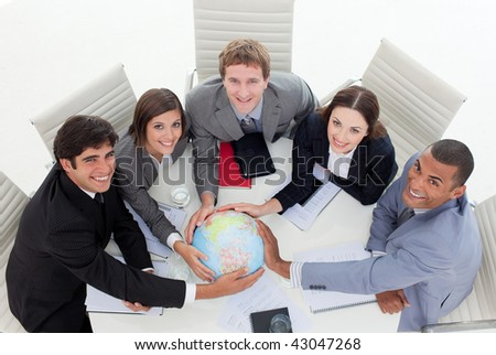 High angle of a diverse business team holding a terrestrial globe in the office - stock photo