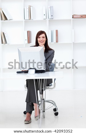 High angle of a smiling businesswoman working at a computer in the office - stock photo