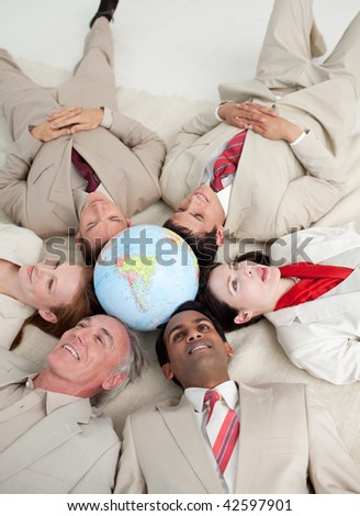 High angle of International business people lying on the floor around a terrestrial globe - stock photo