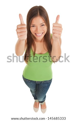 High angle perspective of a happy smiling young woman in jeans looking up at the camera giving giving a double thumbs up of success and approval isolated on white - stock photo