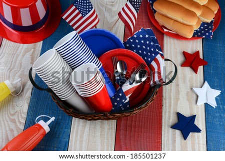 High angle photo of a picnic table ready for Fourth of July Party. The red white and blue table is set with plates, cups, hot dog buns, cups, forks, Uncle Sam Hat, Ketchup and Mustard dispensers. - stock photo