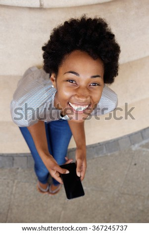 High angle portrait of cheerful young african woman sitting on steps with a mobile phone and looking up - stock photo
