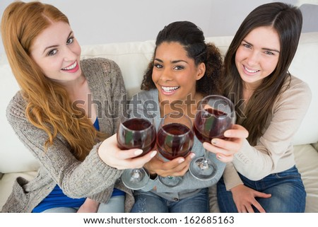 High angle portrait of cheerful young female friends toasting wine glasses on sofa at home - stock photo