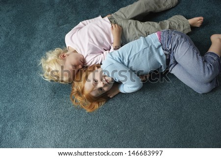 High angle portrait of little girl lying with sister sleeping on carpet at home - stock photo