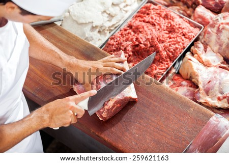 High angle portrait of smiling butcher cutting meat at counter in butchery - stock photo