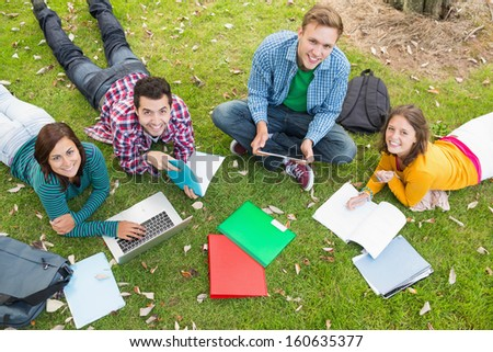 High angle portrait of young college students using laptop while doing homework in the park - stock photo