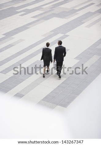 High angle rear view of businesspeople walking in outdoor plaza - stock photo