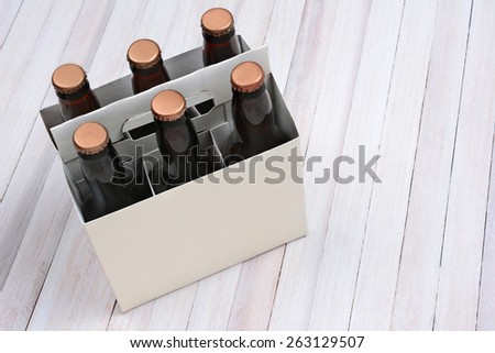 High angle shot of a blank six pack of brown beer bottles on a rustic white wood table. Horizontal format with copy space. - stock photo
