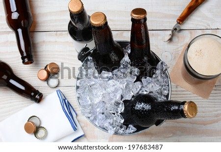 High angle shot of a glass of beer with a metal bucket with unopened bottles. The rustic wood table has empty bottles and caps and an bottle opener. Horizontal Format. - stock photo