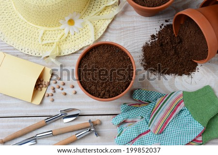 High angle shot of a group of items for potting and planting seeds. Horizontal format on a wooden surface. Items include, shovel, hat, flower pots, soil, gloves, seed packet and more.  - stock photo