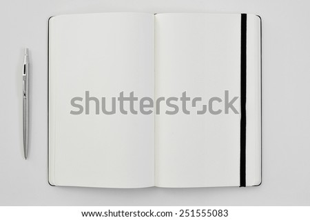high-angle shot of a pen and a blank notepad on a white table - stock photo