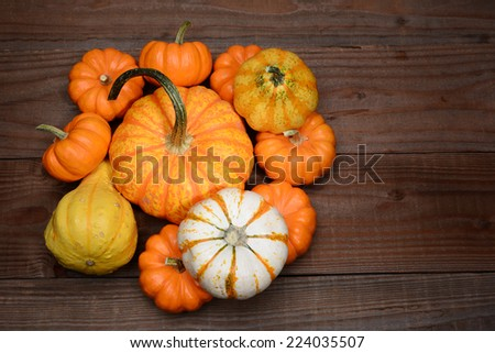 High angle shot of a pile of decorative pumpkins and gourds on a rustic dark wood table. Horizontal format with copy space. - stock photo