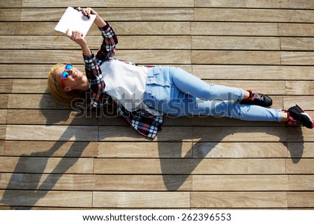 High angle shot of a pretty young woman pouting for a self-portrait while lying on wooden jetty enjoying the sun, cute tourist girl taking self-ie with digital tablet camera outdoors - stock photo