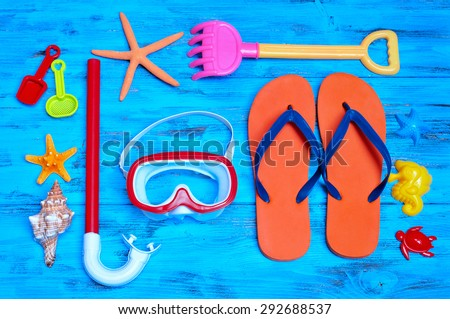 high-angle shot of a rustic blue wooden table full of summer stuff, such as some starfishes, a conch, a diving mask and a snorkel, a pair of flip-flops and some beach toys - stock photo
