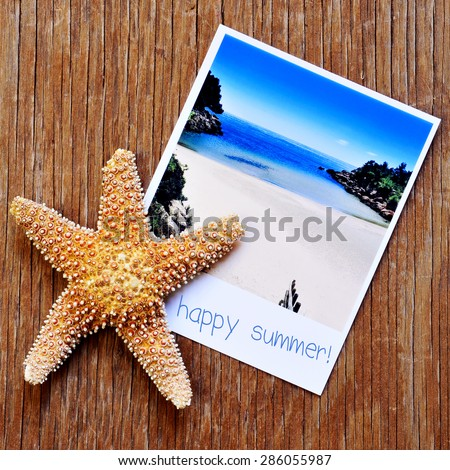 high-angle shot of a starfish and an instant photo of a peaceful beach with the text happy summer written in its frame, placed on a rustic wooden surface - stock photo
