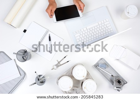 High angle shot of a white desk with primarily white and silver office objects, with a woman holding a tablet computer showing her hands only. Tablet has a blank screen. - stock photo