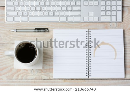High angle shot of a white rustic desk with a modern keyboard, coffee cup and notebook with a coffee stain. Horizontal format. - stock photo