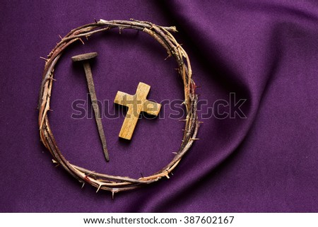 high-angle shot of a wooden christian cross, a rusty nail and the crown of thorns of Jesus Christ, on a purple drapery - stock photo
