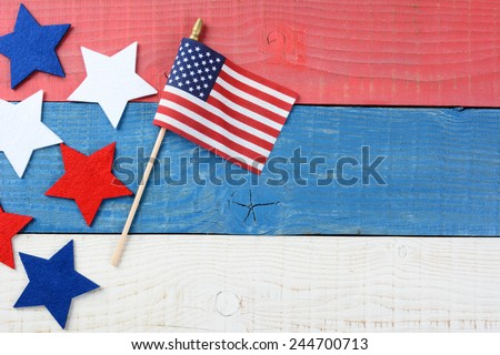 High angle shot of an American Flag and fabric stars on a red, white and blue picnic table. With copy space, perfect for 4th of July and Memorial Day projects. - stock photo