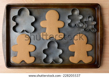 High angle shot of an old baking sheet with Christmas gingerbread man cookies and cookie cutters. Horizontal format on wood kitchen table. - stock photo