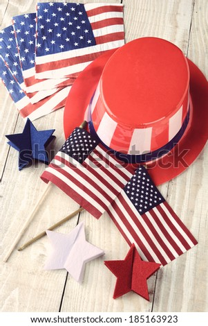 High angle shot of assorted items to celebrate the Fourth of July. Items include, Uncle Sam Hat, American Flags, napkins and red white and blue decorative stars. Vertical format with a vintage look. - stock photo