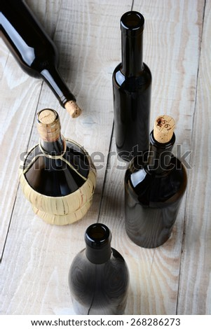 High angle shot of assorted wine bottles on a white rustic wood table. Shallow depth of field with focus on the tops.  - stock photo