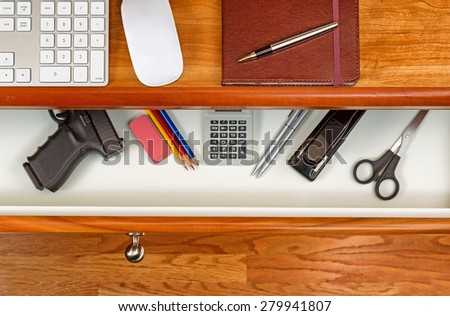 High angle shot of open desk drawer with concealed personal weapon inside. Cherry desktop has computer keyboard, mouse and executive notepad with pen.  - stock photo
