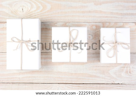 High angle shot of three packages wrapped in plain white paper and tied with white string. Horizontal format on a whitewashed wood table. - stock photo