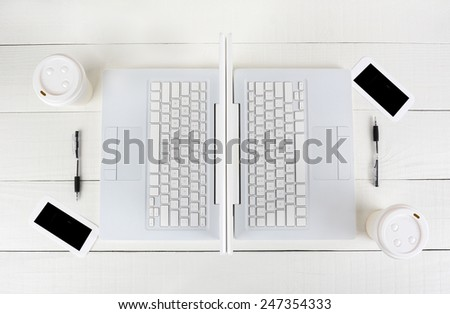 High angle shot of two laptop work stations back-to-back with mirror image identical layouts. Horizontal format on a white wood table. - stock photo