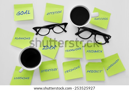 high-angle shot with a pair of cups of coffees and eyeglasses, and some sticky notes with concepts related to teamwork - stock photo