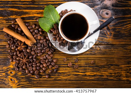 High Angle Still Life of White Cup and Saucer Containing Fresh Brewed Coffee Resting on Rustic Wooden Table Top Scattered with Roasted Coffee Beans, Cinnamon Sticks and Star Anise - stock photo