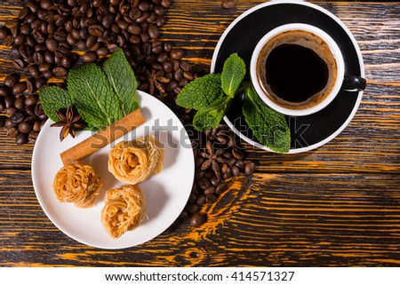 High Angle Still Life View of Black Coffee Served in Black Cup and Saucer Served with Gourmet Pastries and Garnished with Fresh Mint Sprigs on Wood Table Scattered with Roasted Coffee Beans - stock photo