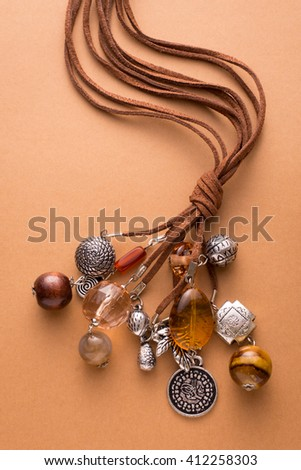 High Angle Still Life View of Handmade Artisan Jewellery on Tan Background - Stylish and Funky Necklace Made with Brown Leather and Adorned with Silver Charms, Wood Beads and Stones - stock photo