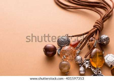 High Angle Still Life View of Handmade Artisan Jewellery on Tan Background with Copy Space - Stylish and Funky Necklace Made with Brown Leather and Adorned with Silver Charms, Wood Beads and Stones - stock photo