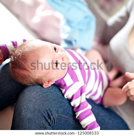 High angle view of a beautiful small baby on its mothers lap standing supported by her knees with shallow dof - stock photo