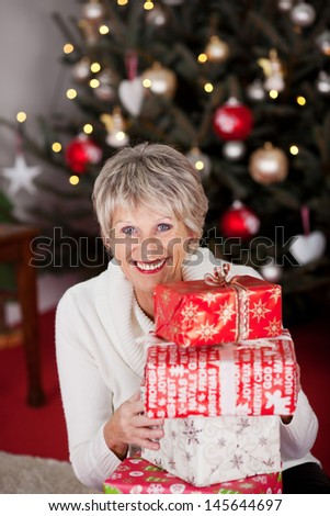 High angle view of a beautiful vivacious happy grandmother with a stack of Christmas gifts sitting in front of a twinkling tree - stock photo