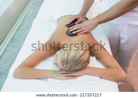 High angle view of a beautiful young woman receiving stone massage at health farm - stock photo