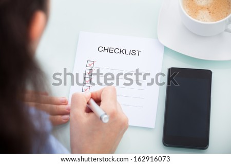 High Angle View Of A Businesswoman Marking On Checklist At Desk - stock photo