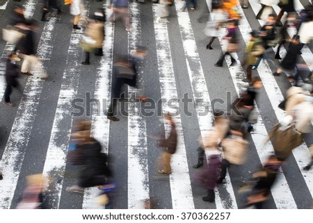 High angle view of a crowd of people walking over a pedestrian crossing with motion blur and focus to the stripes on the road - stock photo