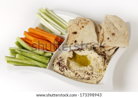 High angle view of a dip tray with hummus, bread, carrot sticks, celery and cucumber. - stock photo