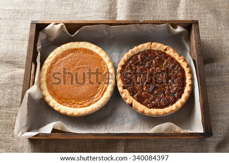 High angle view of a fresh baked pumpkin pie and a pecan pie in a wood box on burlap covered table, for Thanksgiving feast. - stock photo