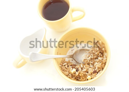 High angle view of a healthy bowl of muesli cereal served with milk and a mug of freshly brewed coffee for breakfast on a white background - stock photo