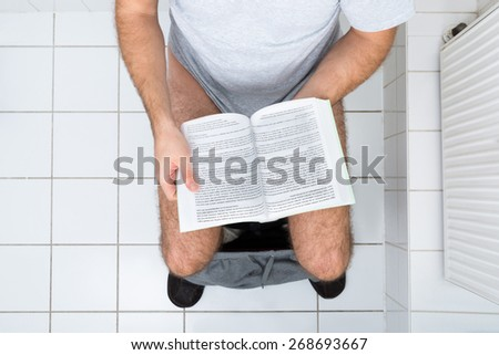 High Angle View Of A Man In Toilet Reading Book - stock photo