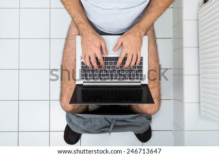 High Angle View Of A Man In Toilet Using Laptop - stock photo