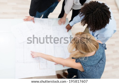 High angle view of a multiethnic business team having a brainstorming session standing around a table discussing plans and paperwork - stock photo