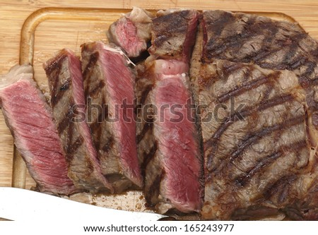 High angle view of a partly-sliced grilled wagyu beef ribeye steak viewed from above - stock photo