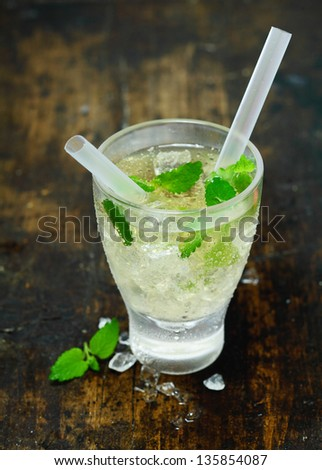 High angle view of a refreshing chilled vodka or gin cocktail Hugo on ice with fresh mint leaves and two straws on an old wooden table top in a bar or nightclub - stock photo