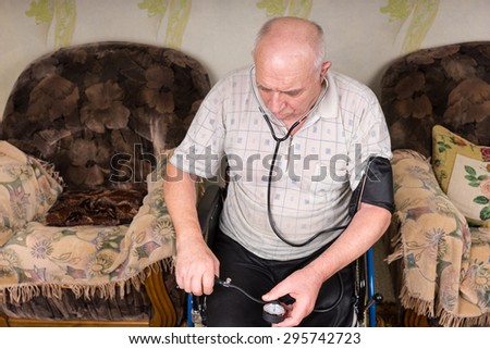 High Angle View of a Senior Bald Man Sitting on his Wheelchair, Checking his Blood Pressure Alone Using Apparatus in the Living Room. - stock photo