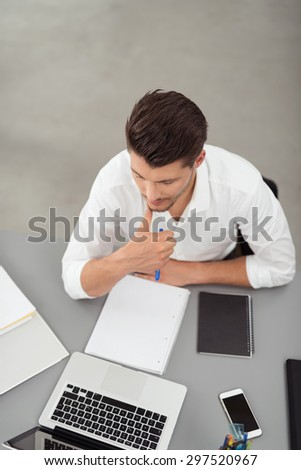 High Angle View of a Serious Young Businessman Sitting at his Desk and Doing Some Research Using his Laptop Computer - stock photo